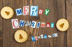 Slogan för glad jul som göras från tidningsbokstäver med kakor Royaltyfria Bilder