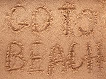 Slogan on a sand. go to beach. A smiley face drawing on a sand Royalty Free Stock Images