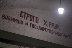Slogan on a wall. On a concrete wall paint has written a slogan, with the hanging bulb stock images