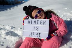 Winter is here. Slogan `winter is here` held by a girl in a snowy landscape Stock Photos