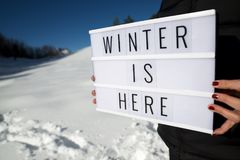 Winter is here. Slogan `winter is here` held by a woman in a snowy landscape Stock Photo