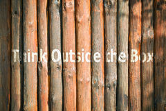 Slogan on wooden planks. Text Think Outside The Box written on wooden background Stock Photography