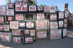 Slogans painted on tv screens. November 17, 205 East Jesus, Slab City, California: a pile of vintage tv's are transformed to art exhibition piece at the outdoor Stock Images