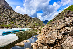Slope of boulders at the water with pieces of ice melting Siberian summer Royalty Free Stock Images