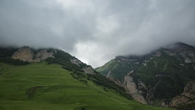 Slope of the Caucasus mountains. In the distance, rain clouds slowly cover the stony mountain slopes. the lush green of the local stock video