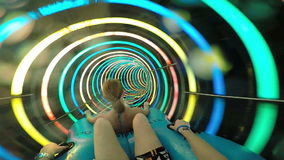 Slope down by water slide in water park. Fun travel inside of the multi color tube at aqua park filmed on action camera stock video