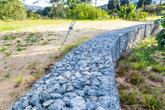 Slope earth retention wall with rocks and wire mesh cage Stock Photo
