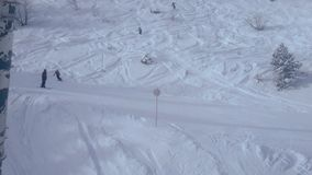 On the slope of the mountain covered with white snow, skiers quickly descend in different directions. People are engaged in mountain skiing and snowboarding on stock footage