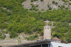 Slope of mountain and medieval tower. Martigny, Valais, Switzerland stock photos
