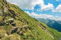 Slope of the mountain ridge. Summer landscape with rocks among grass and clouds on the blue sky. popular destination of Romania Carpathians royalty free stock photo