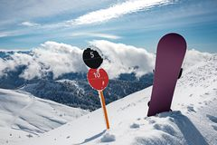 Slope number signs and snowboard at mountains stock images