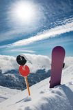 Slope number signs and snowboard at mountains stock image