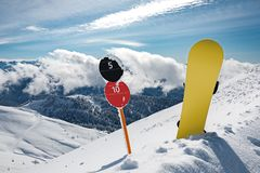Slope number signs and snowboard at mountains royalty free stock image