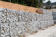 Slope retention management with rocks and wire mesh cage system Royalty Free Stock Images