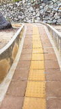 Slope up path of brick walk way decorate with stone wall Stock Photos
