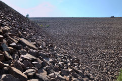 Slope of water dam full of stone Royalty Free Stock Images