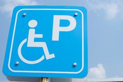 Slope way sign for wheelchair people on blue sky background - Handicapped parking. royalty free stock image