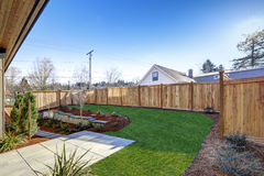 Sloped backyard surrounded by wooden fence Luxury New construction home with open floor plan. Sloped backyard surrounded by wooden fence. Exterior of New Luxury Royalty Free Stock Photo