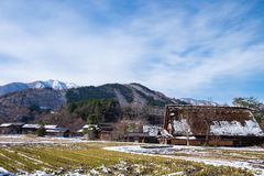 The sloped-roof and thatched-roof houses of snow cover and and rice field that started to melt at Shirakawa-go. Japan stock photography