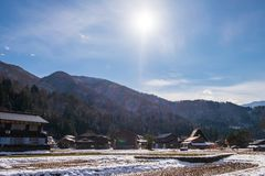 The sloped-roof and thatched-roof houses of snow cover and and rice field that started to melt at Shirakawa-go. Japan royalty free stock images