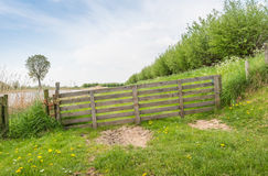 Sloped wooden gate along a dike. Angled wooden gate tied with rope in a rural area along a dike in springtime Stock Photo