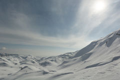 Slopes covered in snow. Snow covered slopes with sun behind clouds in the back Stock Photography