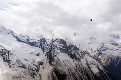 Slopes and peaks, summits of the Caucasus mountains, mountains. Slopes and summits of the Caucasus mountains, mountains in the snow, bird flies over the Stock Image