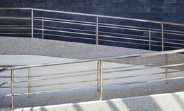 Sloping concrete walkway and steel handrail Royalty Free Stock Photography