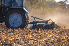 The sloping field. Big blue tractor plow plow the land after harvesting the maize crop on a autumn day. Stock Images