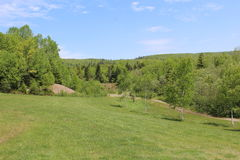A sloping lawn and a dirt path leading towards a quarry in the hills of Cape Breton. A rural scene from Cape Breton Island Royalty Free Stock Image