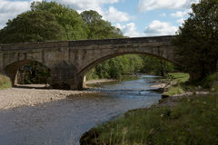 Sloping stone arch bridge in the Yorkshire Dales Royalty Free Stock Photos