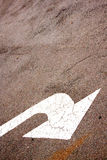 Sloping White Painted Arrow On Asphalt Road Surface Royalty Free Stock Photos
