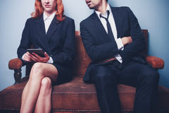 Sloppy businessman spying on successful female coworker Stock Photography