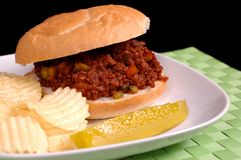 Sloppy Joe sandwich with chips and pickle. On a white plate and bright green mat Stock Images