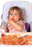 Slordig babymeisje dat spaghetti eet Stock Fotografie