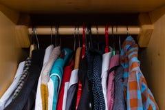 Slordig houten garderobehoogtepunt van kleren Stock Fotografie