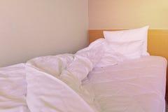 Slordig onopgemaakt bed met hoofdkussen en dekbeddekking stock fotografie
