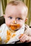 Slordige baby die slab na het eten van stevig voedsel draagt Stock Foto's