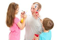 Slordige gezichts schilderende mens en jonge geitjes Stock Foto