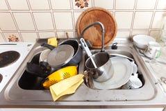 Slordige gootsteen in binnenlandse keuken met vuil aardewerk Stock Foto's