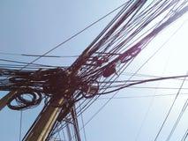 Slordige kabeldraad op elektrische pool tegen blauwe hemel Stock Fotografie