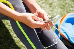 Slose vers le haut de téléphone sportif de participation de femme avec l'écran vide se reposant dessus Photo libre de droits