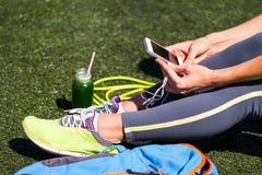 Slose vers le haut de téléphone sportif de participation de femme avec l'écran vide se reposant dessus Images libres de droits