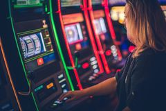 Slot Machine Casino Playing. Caucasian Woman in Her 30s Playing Modern One Handed Bandit Slot royalty free stock photos