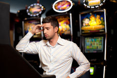 Slot machine looser. Man just loosing at the slot machine, being sad Royalty Free Stock Images