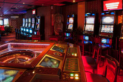 Slot Machine and Roulette. Roulette table and Slot machine. Red lighted casino Royalty Free Stock Image