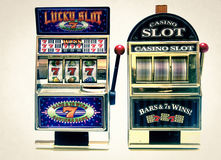 Slot machine. Two vintage toy slot machines with gold money royalty free stock images