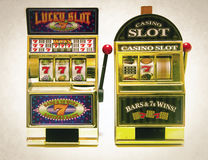Slot machine. Two vintage toy slot machines with gold money royalty free stock image