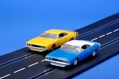 Slot racing cars. Two Dodge Charger slotcars racing on a Carrera slot racing track Stock Image