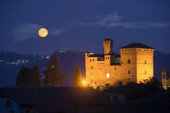 Slott av Grinzane Cavour i nattligt med en fullmåne fotografering för bildbyråer